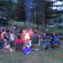 Singing songs around the fire accompanied by guitars, banjos, violin, and flute.
